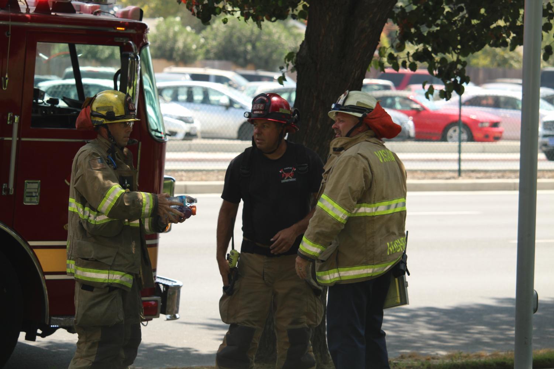 The Visalia Fire Department confers on the scene.