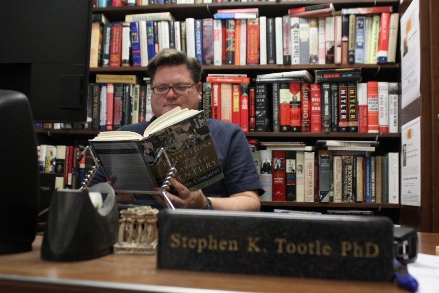 Stephen+Tootle+reads+%22Reflections+on+a+Ravaged+Century%22+as+one+of+his+many+favorites+to+pick+from+his+various+collections.