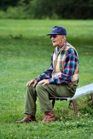 An older man watching his kids play baseball